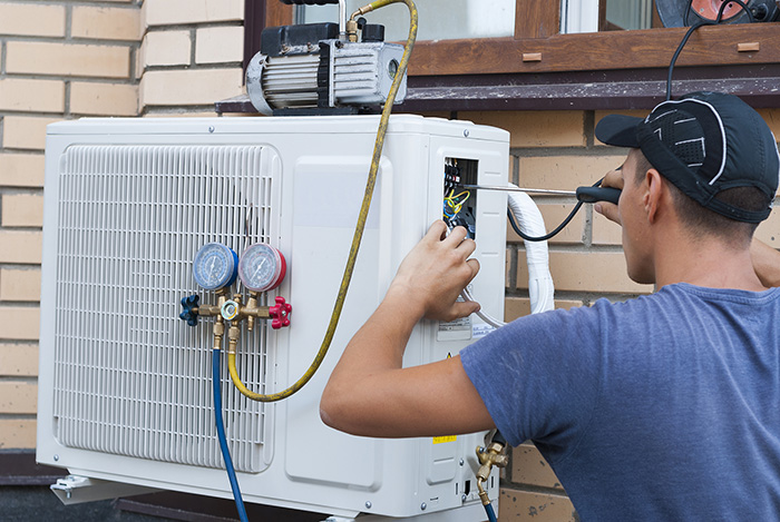 Man repairing a ductless AC unit outside